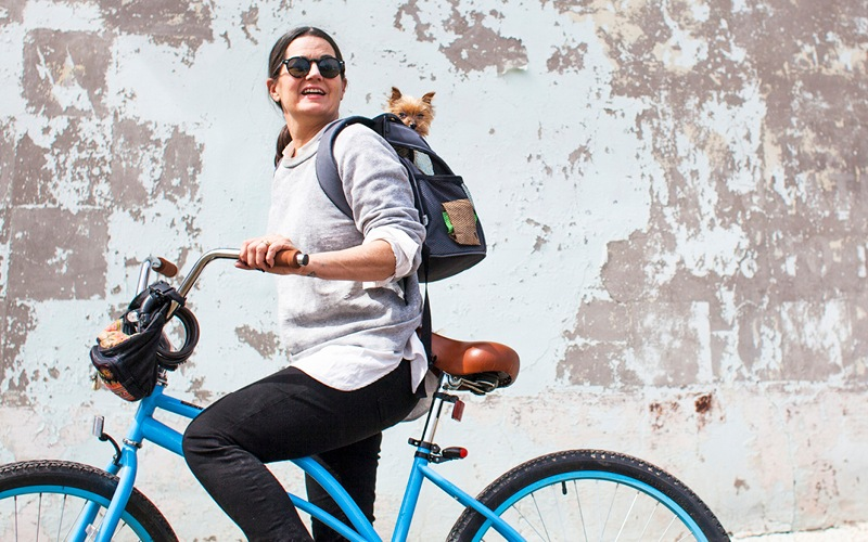 woman on bicycle with a dog in her backpack